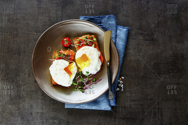 Smoked salmon toasts with micro greens and poached eggs over concrete background