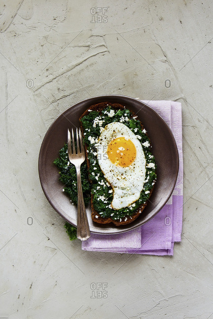 Fried egg sandwich with rye bread, kale and feta cheese on concrete background