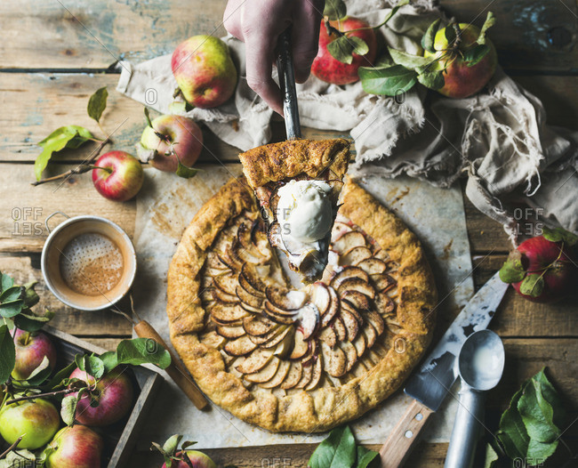 Man's hand holding piece of apple crostata with cinnamon and ice-cream scoop