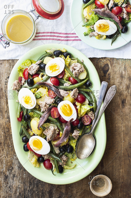 Salad nicoise with romain lettuce, cherry tomatoes, tuna, green beans, black olives, anchovies and hard-boiled eggs