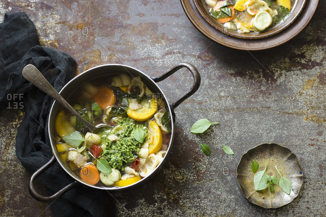 Summer minestrone soup with squash, carrot, tomatoes, basil pesto, broad bean and pasta shells
