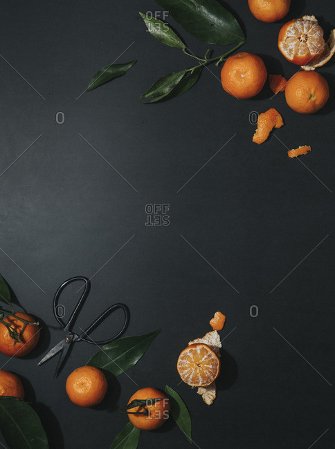 Mandarins, whole and peeled on a black surface (seen from above)
