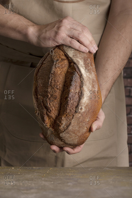 Man holding a freshly baked loaf of bread