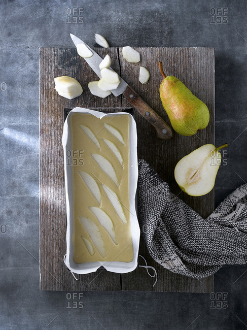 Top view of ingredients and products for preparing sweet pear cake arranged on wooden board