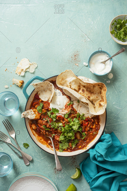 Bean chilli with tomatoes, peppers, garlic and smoked paprika, sour cream, coriander and flatbreads