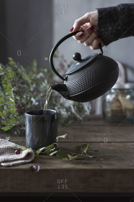Hand of unrecognizable person pouring tea from pot to cup on a table