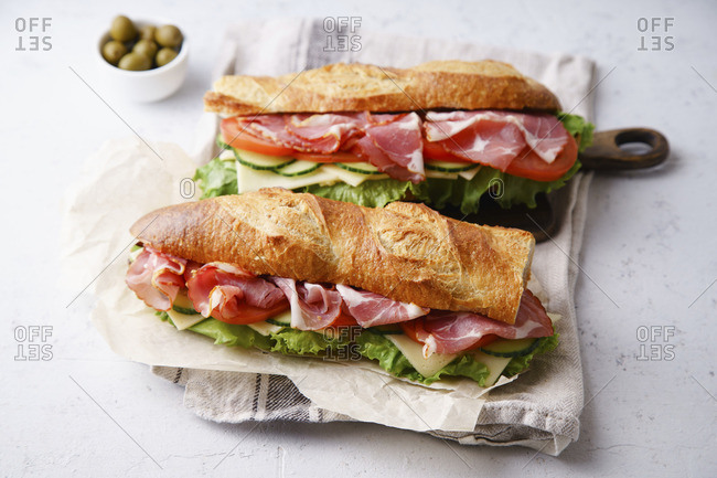 Side view of two fresh baguette sandwiches bahn-mi styled with ham, sliced cheese, tomatoes and fresh lettuce