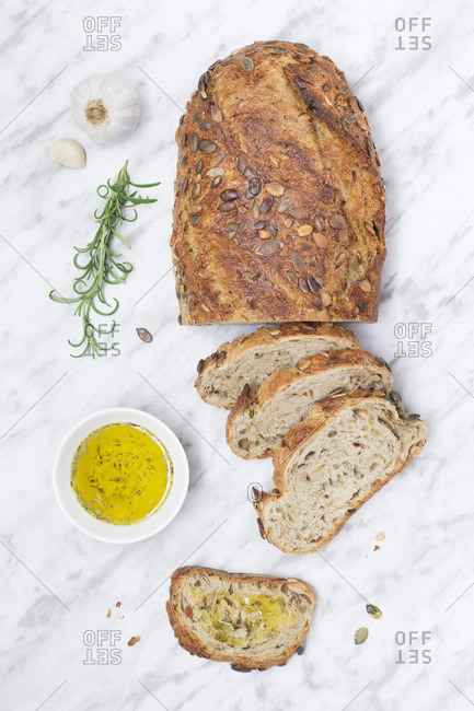 Fresh baked loaf of bread with seeds and bowl of olive oil