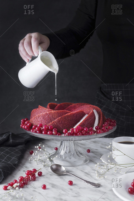 Woman serving and pouring cream on sweet red cake