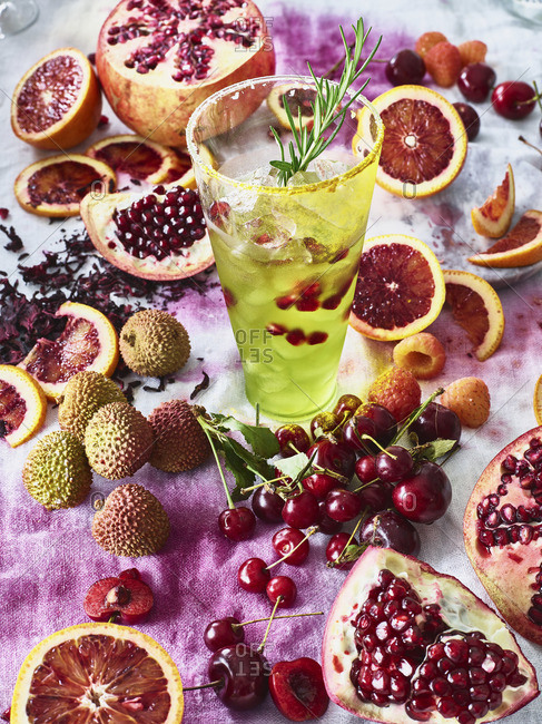A green cocktail in a glass with pomegranate and rosemary