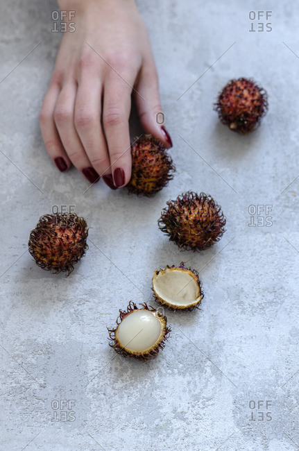 The girl stretches out her hand and takes rambutan