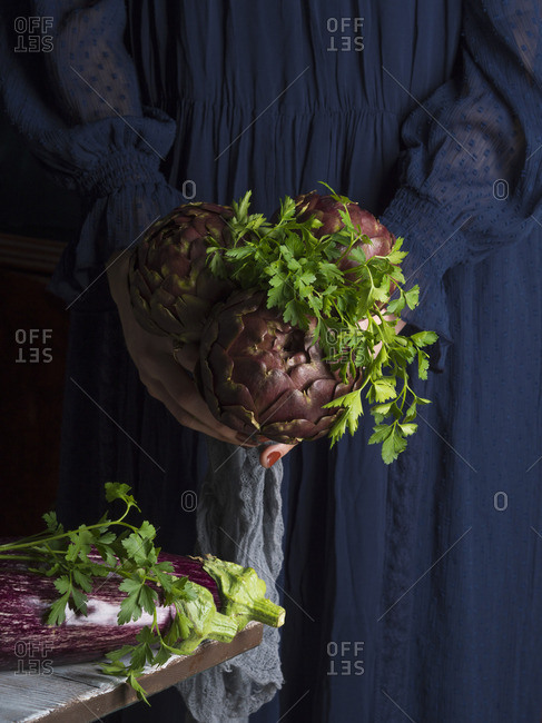 Woman in blue dress holding a bunch of artichokes with parsley and aubergines on the table