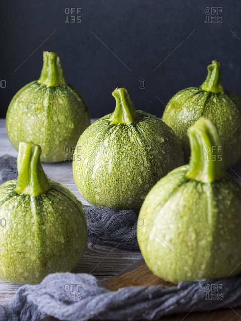 Raw round zucchini on wooden table