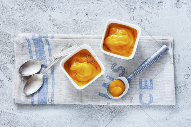 Mango sorbet in a bowl with an ice cream scoop