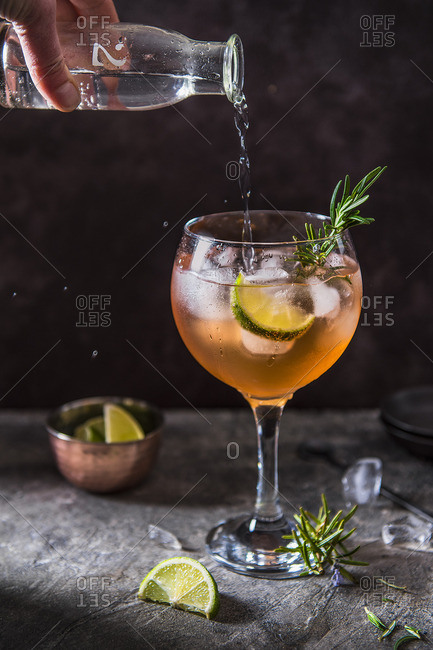 Pink gin cocktail with angostura bitters, lime and rosemary, tonic water beeing poured