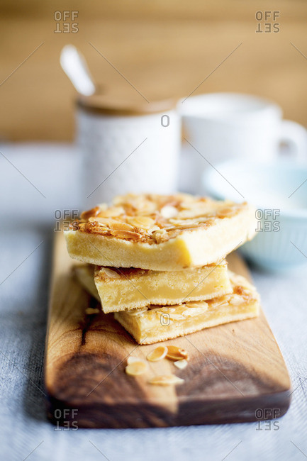 A stack of butter cake slices with flaked almonds