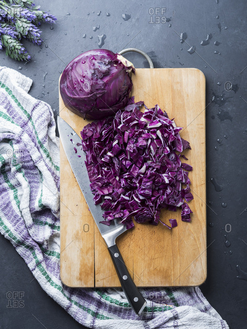 Cutting purple cabbage on wooden board