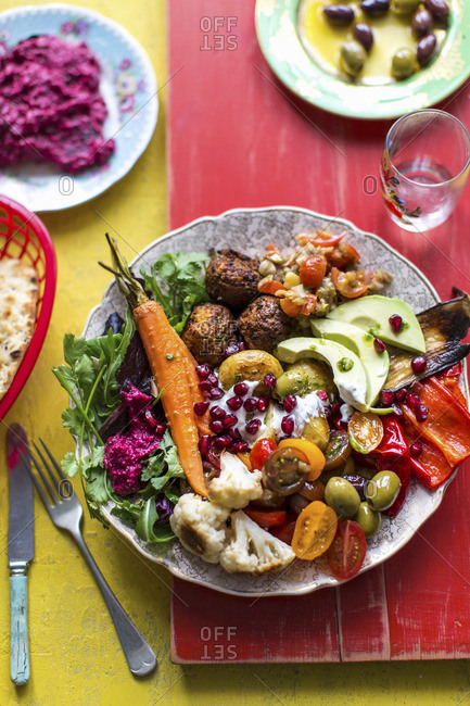 Beetroot hummus, falafel, flat bread, mezze, mutabal, olives, peppers, pommigranet, roast carrots, roast cauliflower, roast potates, salad