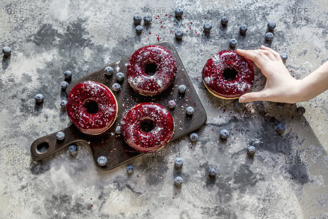 A hand taking a doughnut with blueberry glaze and glitter powder