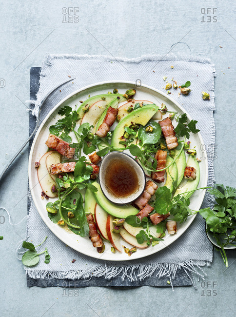 Apple and avocado salad with ginger bacon strips, watercress and pistachios