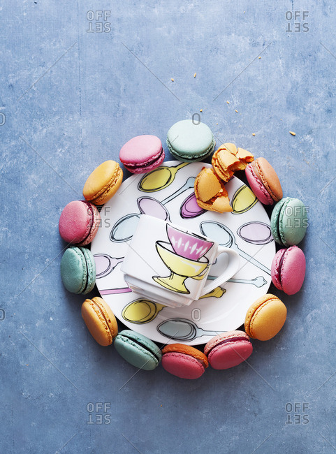 Colourful macaroons around a plate and a cup