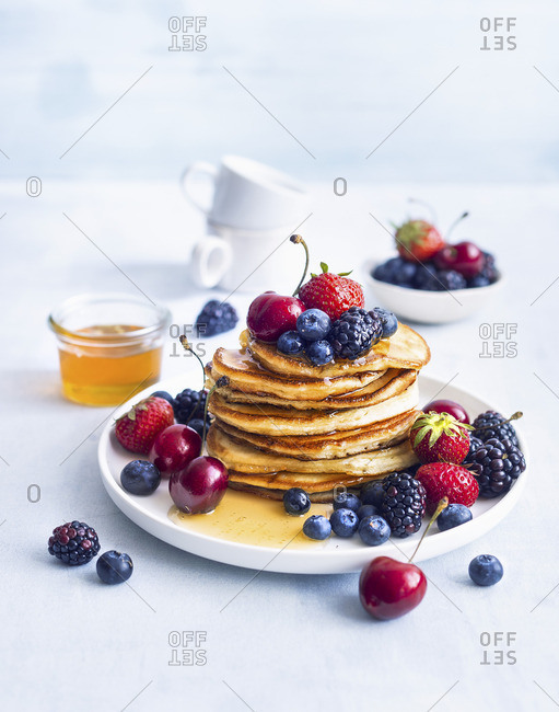 Pancakes with colourful berries and honey