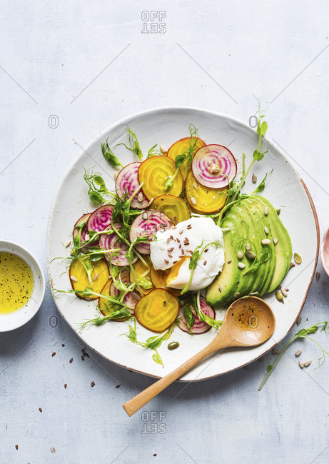 Vegetable salad with avocado and eggs Benedict