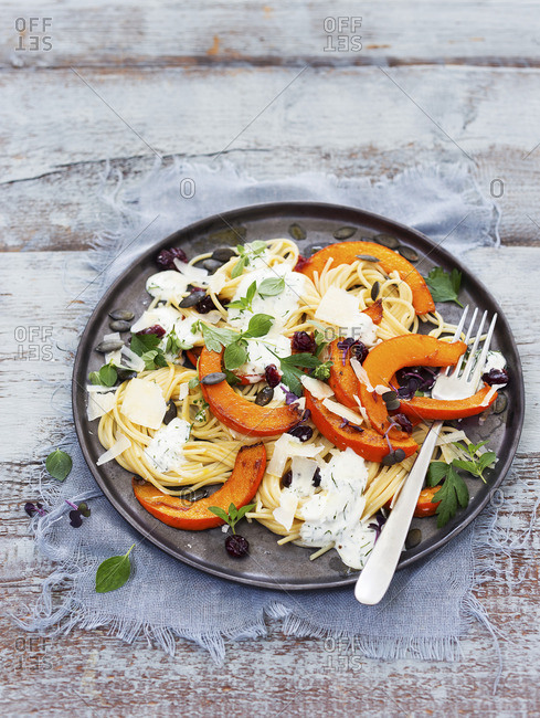 Spaghetti with baked pumpkin wedges and a yoghurt and herb sauce