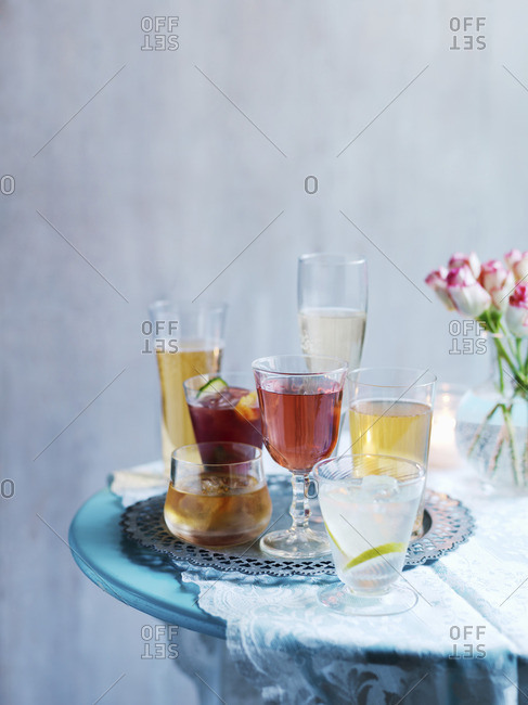 Various cocktails on a table with a flower vase