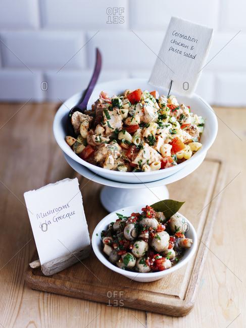 Pasta salad with coronation chicken and Greek mushroom salad
