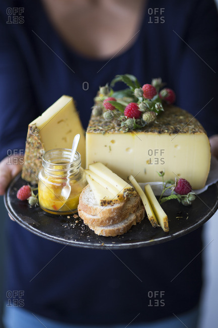 A woman holding a tray of wild herb cheese, bread and chutney