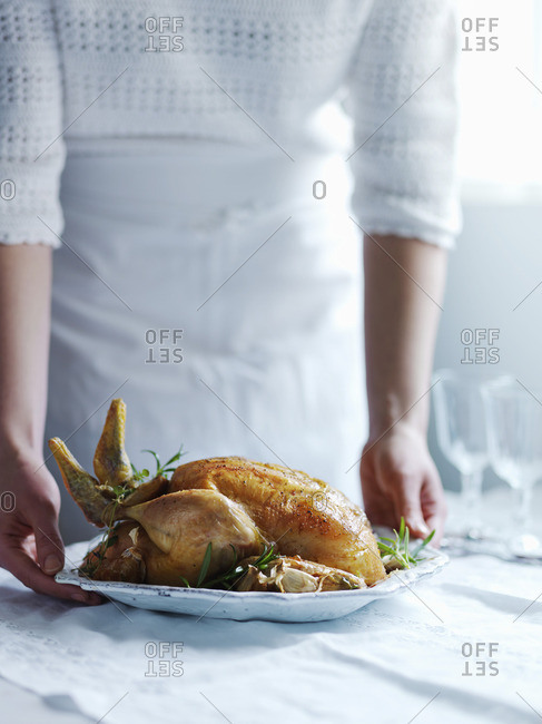A woman serving roast chicken with thyme