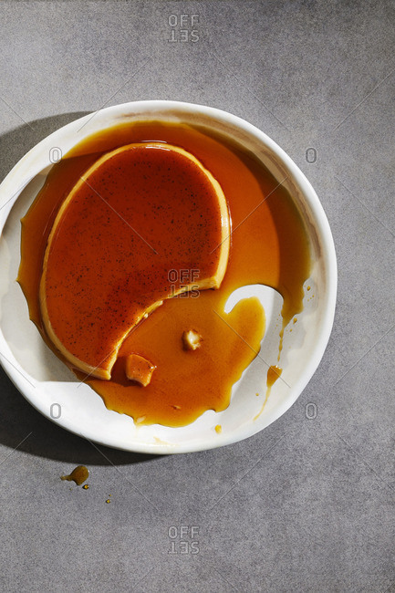 Creme caramel with a piece missing on a white place with sauce