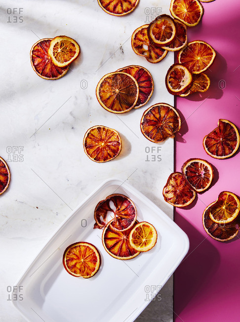 Dried Oranges on a marble and pink background with a plate