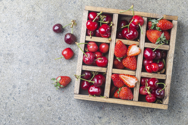 Mix of fresh berries in vintage wooden box on rustic background
