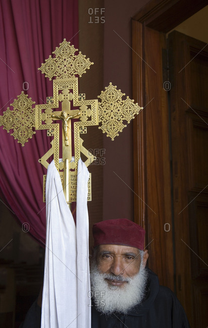 Addis Ababa, Ethiopia - January 17, 2007: Christian priest holding ornate gold crucifix