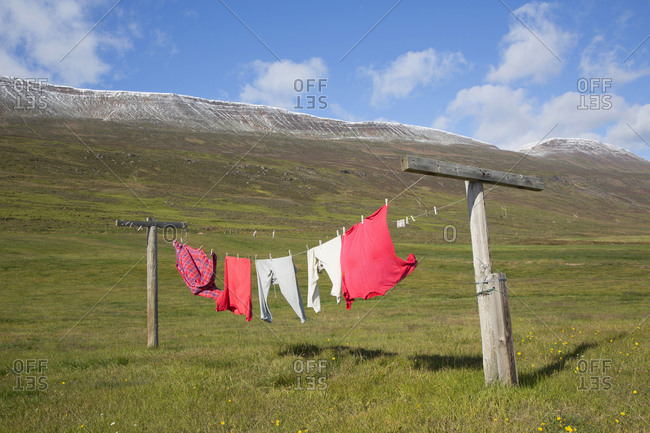 Man's drying laundry on clothesline in the Northern Region, Iceland