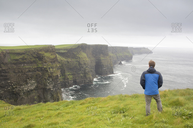 Tourists enjoying view of the Cliffs of Moher on rainy day, Ireland