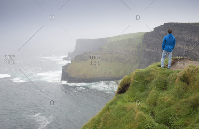 Man enjoying the view of the Cliffs of Moher on rainy day, Ireland