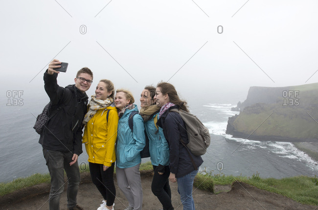 Ireland - May 31, 2019: Tourists taking selfie with view of the Cliffs of Moher on rainy day