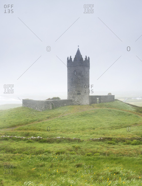 Doonagore Castle tower surrounded by fog in Kerry County, Ireland
