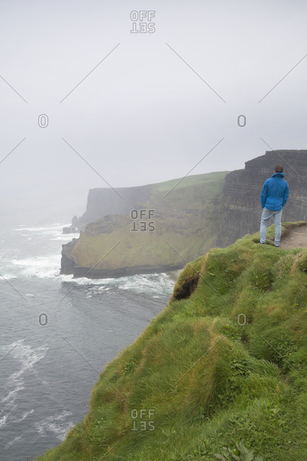 Man enjoying view of the Cliffs of Moher on rainy day, Ireland