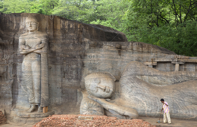 Polonnaruwa, Sri Lanka - October 23, 2012: Reclining Buddha at the Gal Vihara temple with man sweeping