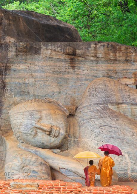 Father and son praying by reclining Buddha at the Gal Vihara temple, Polonnaruwa, Sri Lanka