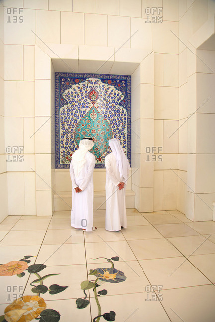 Abu Dhabi, United Arab Emirates - September 14, 2012: Two men looking at tile detail at the Sheikh Zayed Mosque