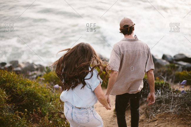 Young couple walking toward the ocean holding hands