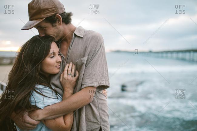 Couple cuddling on the beach at sundown