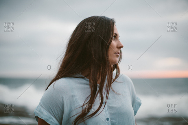 Young brunette woman looking to the side in front of the ocean horizon