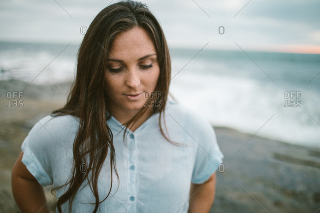Young woman wearing blue looking peacefully by the ocean