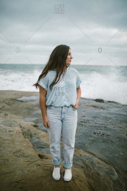 Young fashionable woman standing by the ocean wearing denim and blue